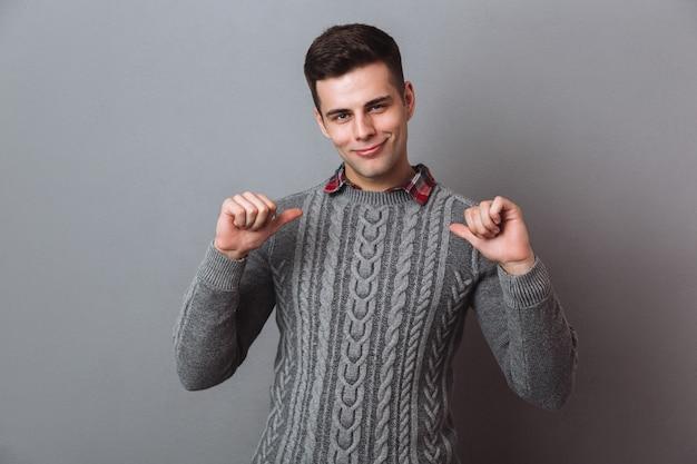 De glimlachende donkerbruine mens in sweater wijst op zich en kijkend
