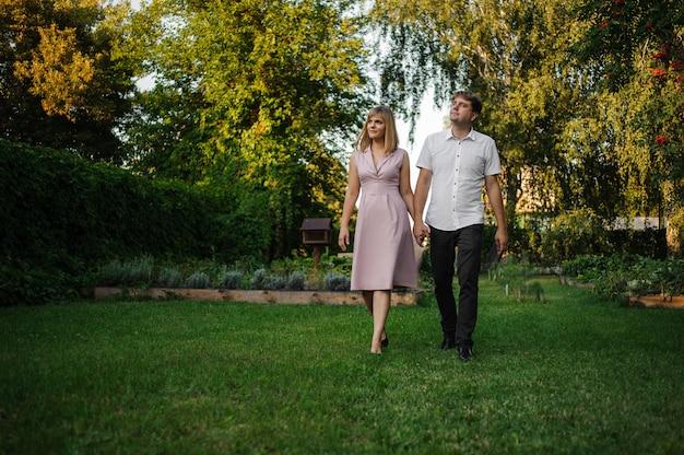De glimlachende echtgenoot en de vrouw die op de grasholding lopen dienen het groene park onder boomtakken in