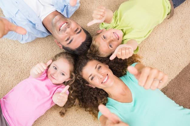 De glimlachende familie die op de deken in cirkel het liggen liggen beduimelt omhoog