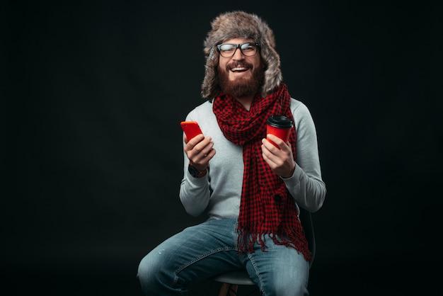 De glimlachende gebaarde hipster die warme de winterkleren dragen zit op een stoel, houdt rode dingen zoals telefoon vast en haalt kop koffie of thee weg.
