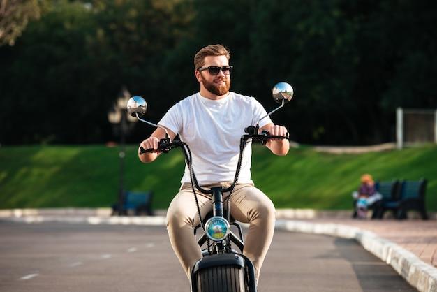 De glimlachende gebaarde mens in zonnebril berijdt in openlucht op moderne motor en weg kijkend