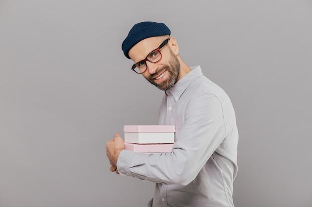 De glimlachende gebaarde mens met gelukkige uitdrukking, donker varkenshaar, draagt wit overhemd en bril