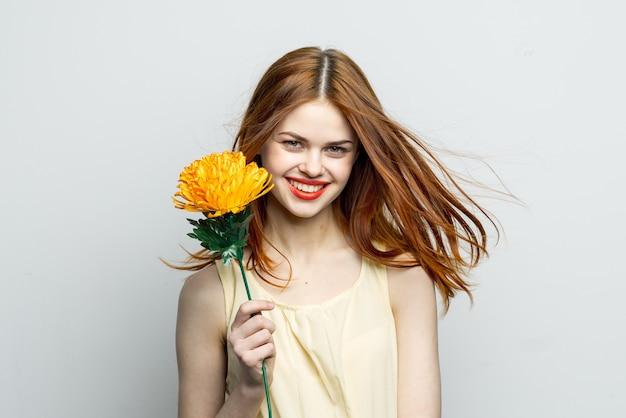 De glimlachende gele bloem van vrouwen rode lippen in handen van het model van de charmegift. hoge kwaliteit foto
