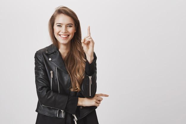 De glimlachende gelukkige, aantrekkelijke vrouw heft wijsvinger op heeft idee