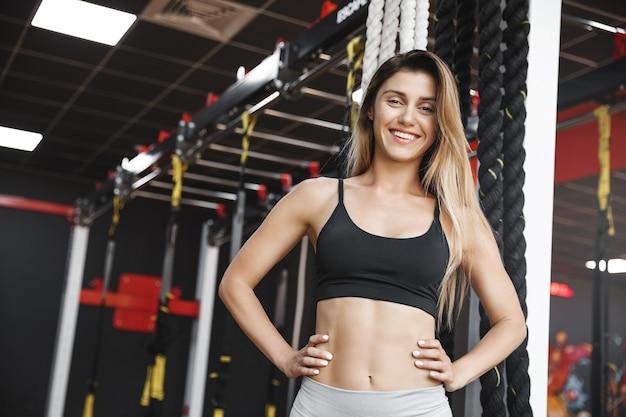 De glimlachende gelukkige en ontspannen jonge onbezorgde sportvrouw in zwarte sportbeha en leggigns, houdt handen op taille.