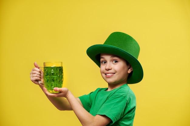 De glimlachende gelukkige kaukasische jongen in ierse groene hoed houdt een glas met groene drank stelt op camera
