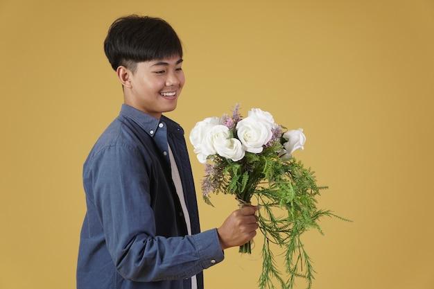 De glimlachende gelukkige vrolijke jonge aziatische mens kleedde terloops geïsoleerd houden bloemboeket.