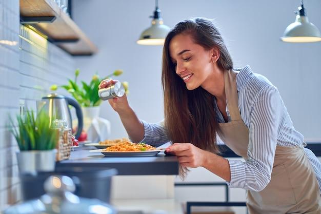 De glimlachende gelukkige vrolijke leuke kokende zouten van de vrouwenhuisvrouw en bereidt voedsel voor diner