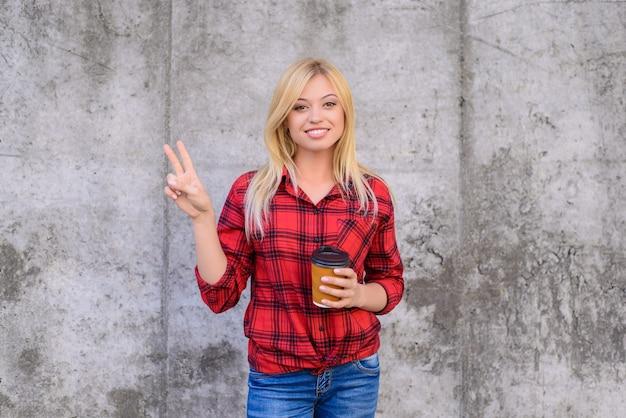 De glimlachende gelukkige vrouw met blond haar gekleed in vrijetijdskleding vertoont overwinningsteken en houdt 's ochtends koffie