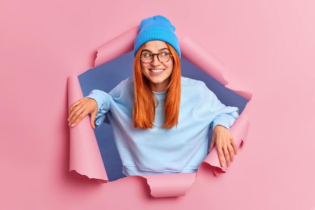 De glimlachende gember jonge europese vrouw met blije uitdrukking kijkt weg en toont gelukkig grote belangstelling draagt een blauwe hoed en een trui met lange mouwen.