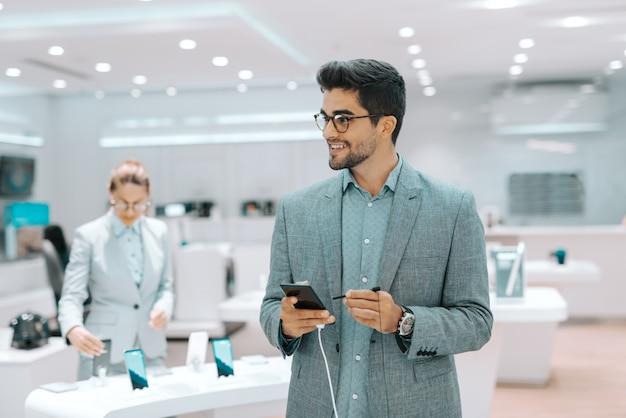 De glimlachende gemengde ras gebaarde mens kleedde zich in formele slijtage die slimme telefoon uitproberen en weg kijken. tech store interieur.