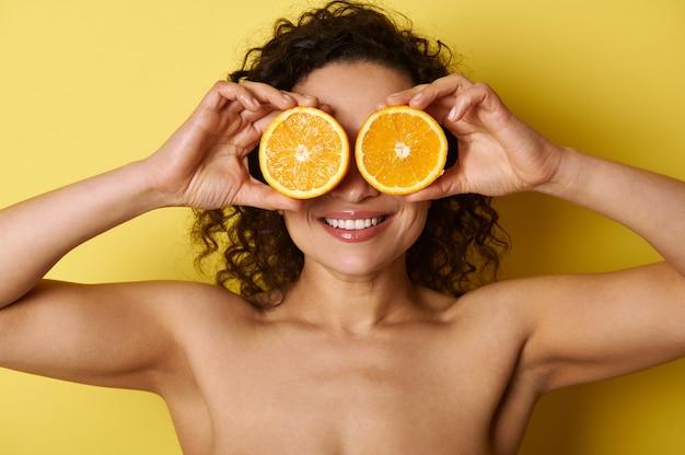 De glimlachende gezonde glimlach van de gemengde race, de gespierde vrouw en de stralende, gehydrateerde gezichtshuid, die haar ogen bedekt met zoete oranje helften