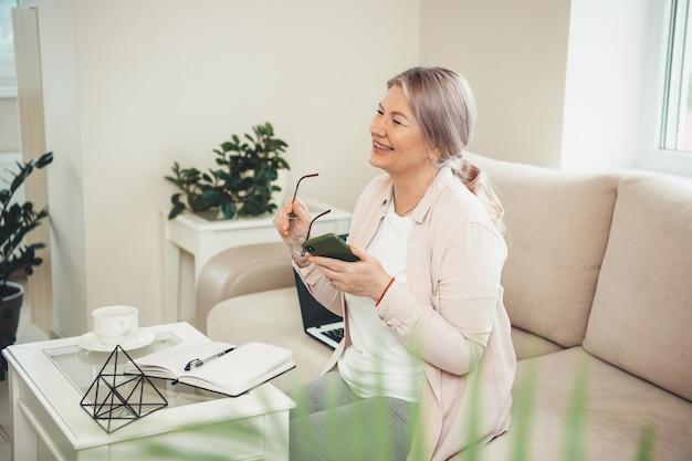 De glimlachende hogere vrouw die een bril draagt, houdt een telefoon vast terwijl hij op de bank zit en met iemand bespreekt