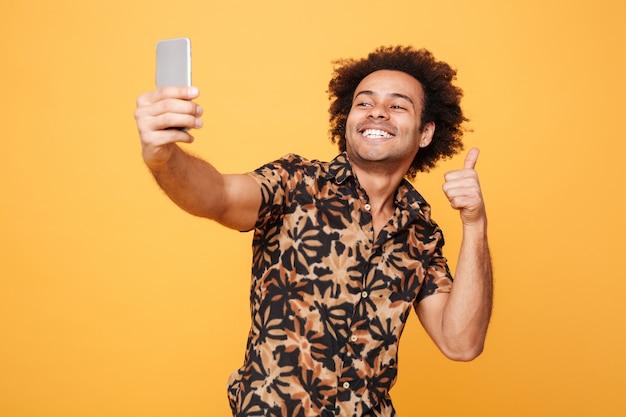 De glimlachende jonge afrikaanse mens maakt selfie terwijl het tonen van duimen
