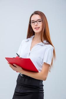 De glimlachende jonge bedrijfsvrouw met pen en tablet voor nota's over grijs
