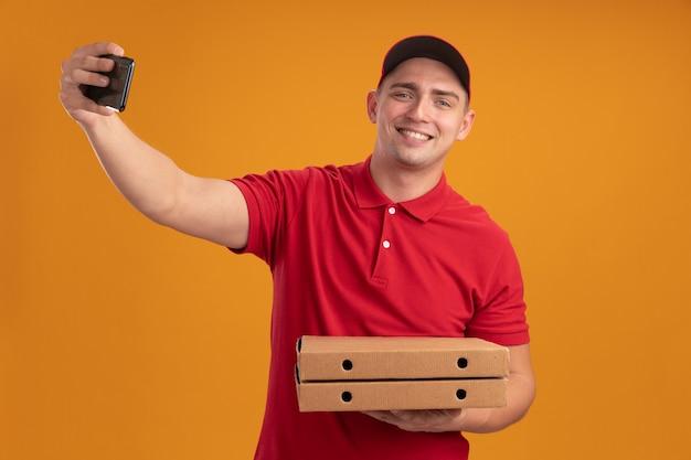 De glimlachende jonge bezorger die uniform met pet draagt die pizzadozen houdt neemt een selfie die op oranje muur wordt geïsoleerd