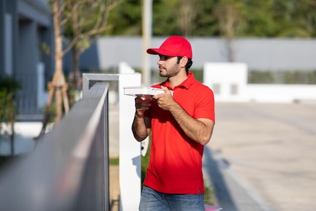 De glimlachende jonge bezorger in rood uniform die een doos houdt geeft aan mooie vrouwenklant voor het huis.