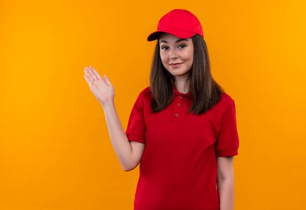 De glimlachende jonge bezorgvrouw die een rood t-shirt in een rode pet draagt, wijst naar de kant met haar hand op geïsoleerde oranje muur
