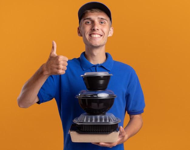 De glimlachende jonge blonde bezorger duimen omhoog en houdt voedselcontainers op sinaasappel