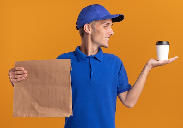 De glimlachende jonge blonde bezorger houdt document pakket vast en bekijkt kop op sinaasappel