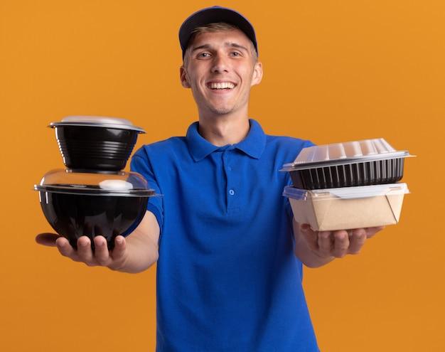 De glimlachende jonge blonde bezorger houdt voedselcontainers op sinaasappel