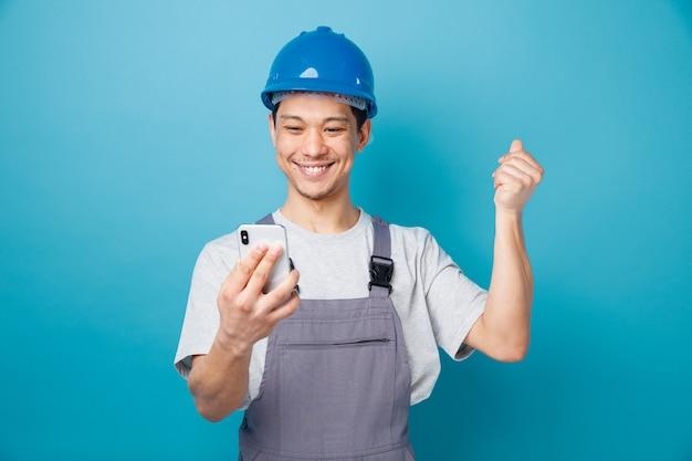 De glimlachende jonge bouwvakker die veiligheidshelm en eenvormig bedrijf draagt en het houden van mobiele telefoon bekijkt dient lucht in