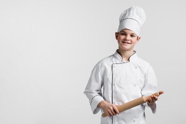 De glimlachende jonge deegrol van de jongensholding met exemplaarruimte