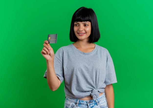 De glimlachende jonge donkerbruine kaukasische vrouw houdt creditcard die kant bekijkt die op groene achtergrond met exemplaarruimte wordt geïsoleerd