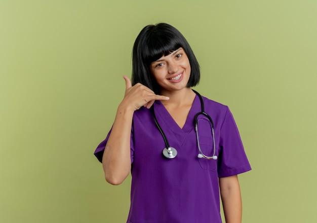 De glimlachende jonge donkerbruine vrouwelijke arts in uniform met stethoscoopgebaren noemt me handteken dat op olijfgroene achtergrond met exemplaarruimte wordt geïsoleerd