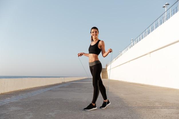 De glimlachende jonge gelukkige sportenvrouw maakt sportoefeningen