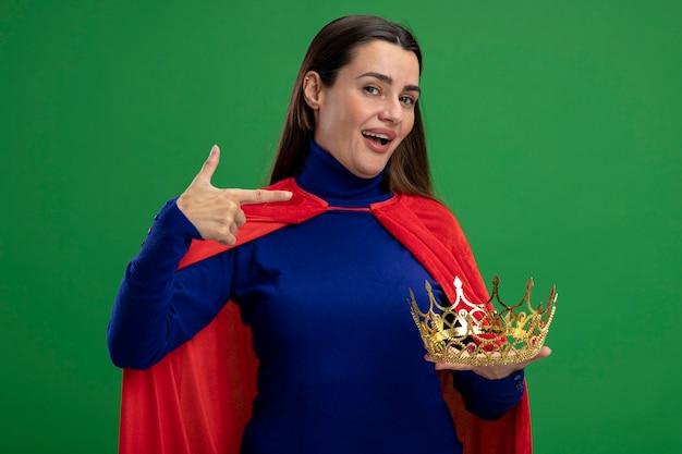 De glimlachende jonge holding van het superheromeisje en wijst op kroon die op groen wordt geïsoleerd