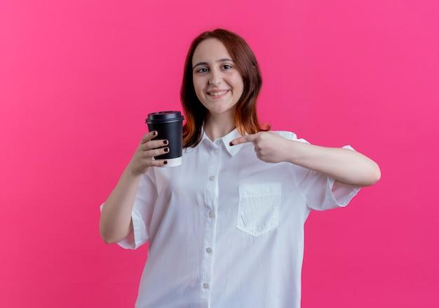 De glimlachende jonge holdings van het roodharigemeisje en wijst op kop van koffie die op roze wordt geïsoleerd