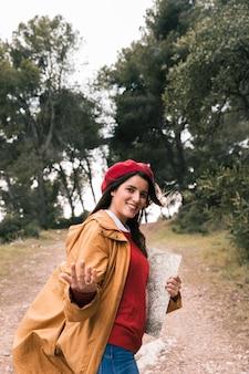 De glimlachende jonge kaart van de vrouwenholding in de hand die vraaggebaar maakt