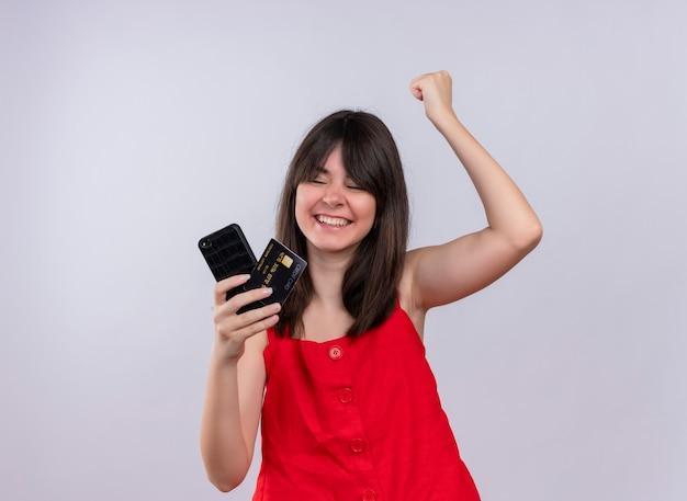 De glimlachende jonge kaukasische telefoon en de creditcard van de meisjesholding bij elkaar en het opheffen van vuist die telefoon op geïsoleerde witte achtergrond bekijken