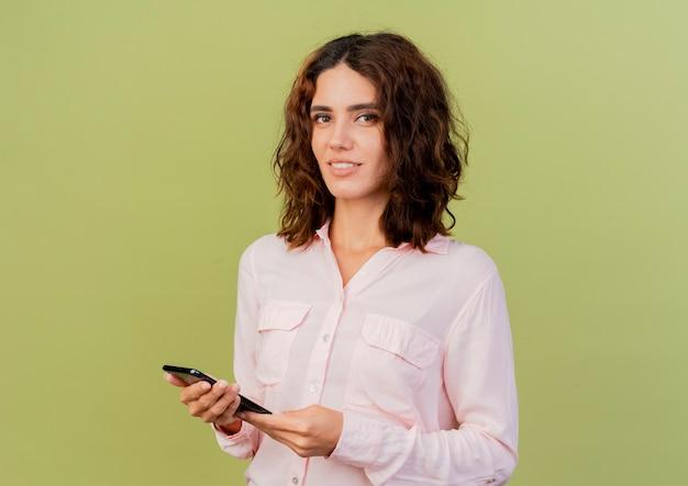 De glimlachende jonge kaukasische vrouw houdt telefoon die camera bekijkt die op groene achtergrond met exemplaarruimte wordt geïsoleerd