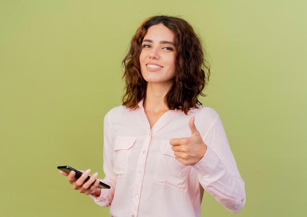 De glimlachende jonge kaukasische vrouw houdt telefoon en duimen omhoog geïsoleerd op groene achtergrond met exemplaarruimte