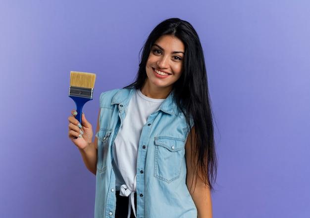 De glimlachende jonge kaukasische vrouw houdt verfborstel die camera bekijkt die op purpere achtergrond met exemplaarruimte wordt geïsoleerd