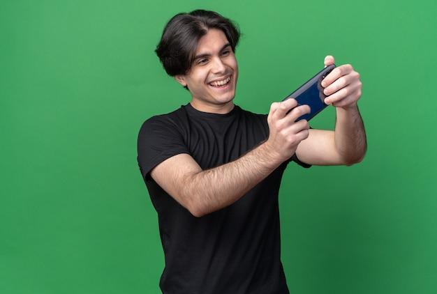 De glimlachende jonge knappe kerel die zwart t-shirt draagt, neemt een selfie die op groene muur met exemplaarruimte wordt geïsoleerd