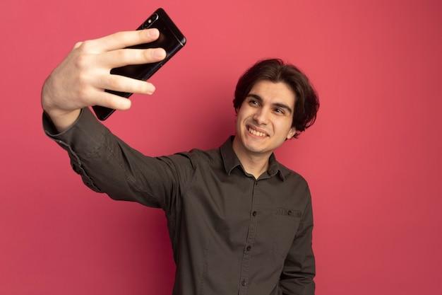 De glimlachende jonge knappe kerel die zwart t-shirt draagt, neemt een selfie die op roze muur wordt geïsoleerd