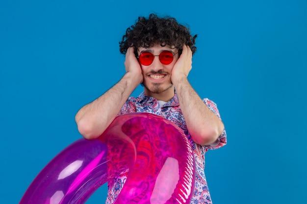 De glimlachende jonge knappe krullende mens die zonnebril draagt die zwemring houdt die handen op oren op geïsoleerde blauwe muur met exemplaarruimte houdt