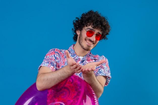 De glimlachende jonge knappe krullende mens die zonnebril draagt die zwemring houdt die uit handen op geïsoleerde blauwe muur met exemplaarruimte strekt