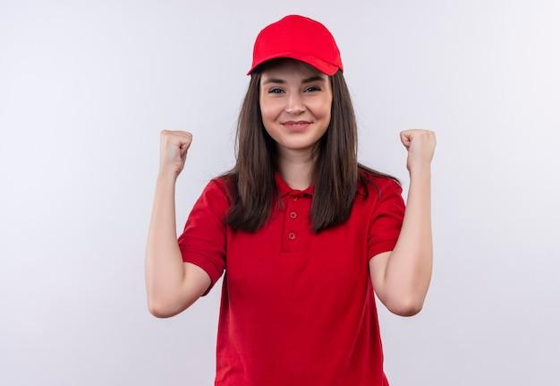 De glimlachende jonge leveringsvrouw die rode t-shirt in rood glb draagt hief haar pasvormen op geïsoleerde witte muur op