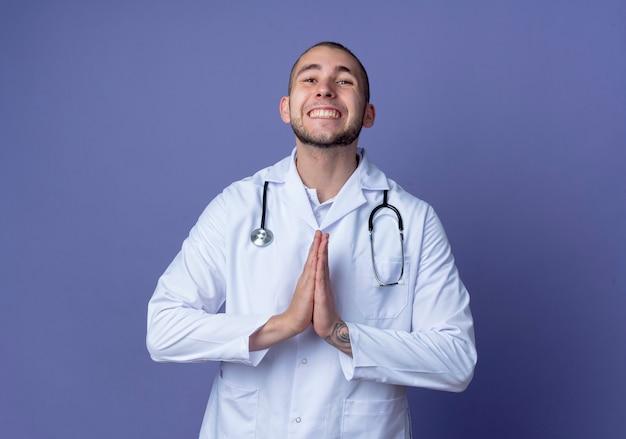 De glimlachende jonge mannelijke arts die medisch kleed en een stethoscoop om zijn hals draagt, dient bidgebaar in dat op purpere muur wordt geïsoleerd