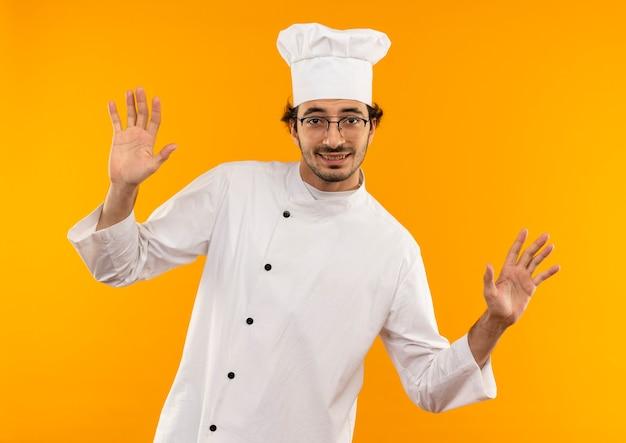 De glimlachende jonge mannelijke kok die eenvormige chef-kok draagt en glazen spreidt handen uit die op gele muur worden geïsoleerd