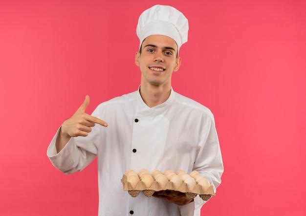 De glimlachende jonge mannelijke kok die eenvormige chef-kok draagt wijst vinger aan partij eieren in zijn hand met exemplaarruimte