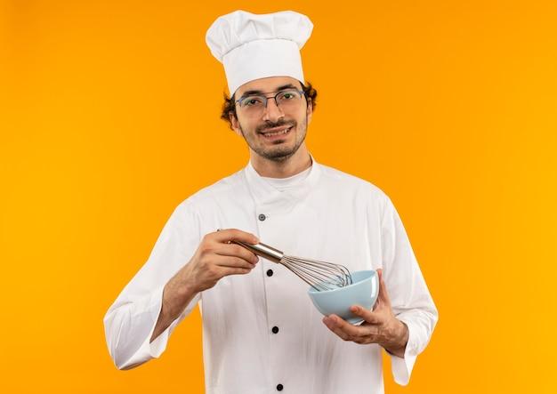 De glimlachende jonge mannelijke kok die eenvormige chef-kok en de glazenholding draagt ?? zwaait en kom geïsoleerd op gele muur