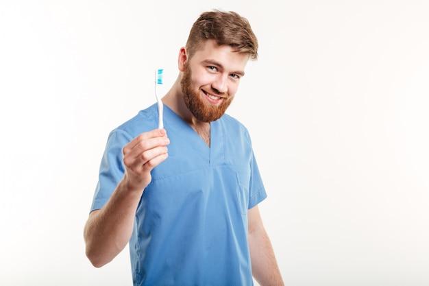 De glimlachende jonge mannelijke tandenborstel van de tandartsholding