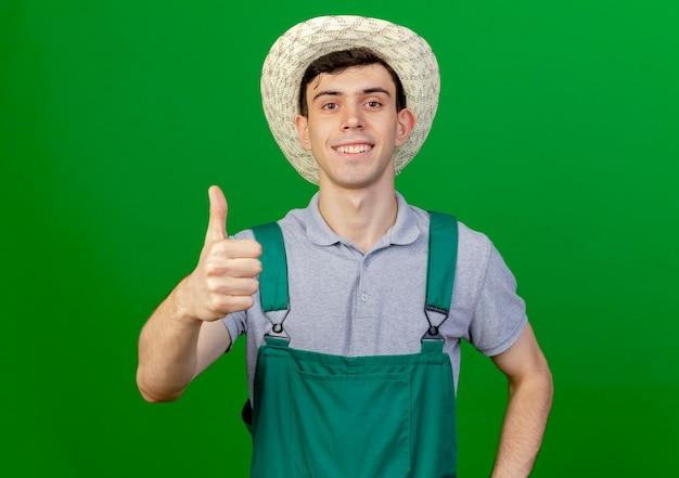 De glimlachende jonge mannelijke tuinman die het tuinieren hoed draagt beduimelt omhoog geïsoleerd op groene achtergrond met exemplaarruimte