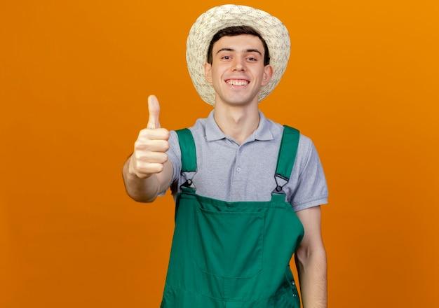 De glimlachende jonge mannelijke tuinman die het tuinieren hoed draagt beduimelt omhoog