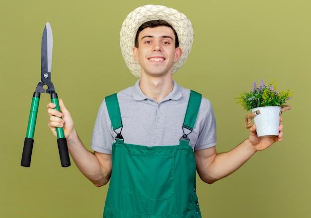 De glimlachende jonge mannelijke tuinman die het tuinieren hoed draagt houdt tondeuse en bloemen in bloempot